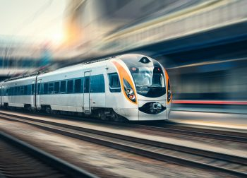 Beautiful train in motion at the railway station at sunset in Europe. Modern intercity train on the railway platform with motion blur effect. Industrial scene with moving passenger train on railroad